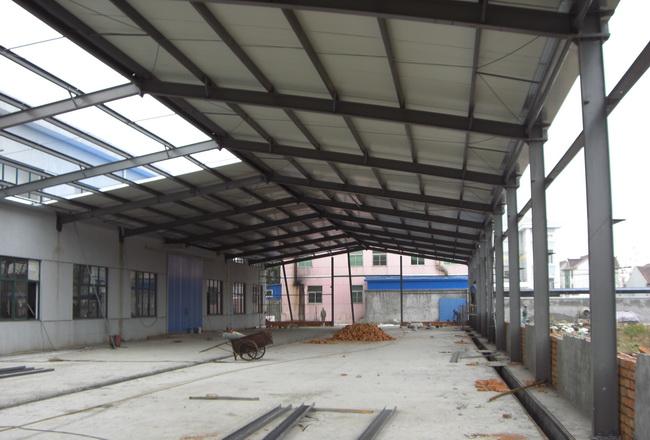 该项目是上海彬煌钢结构有限公司全程设计与安装,客户是因为生产时,厂房不够用,要求是在原有的厂房外侧加宽,而且不影晌原来的生产进度。考虑到原来的厂房是混凝土钢筋结构,承重能力强,因此在靠近原厂房一侧,并没有设计立柱,而是直接用化学螺栓连接到原来的水泥柱上,这样既节省了造价,又增加了实用面积,而且施工期短,可谓是一举三得。主体框架部分还是采用钢结构,外墙是1.